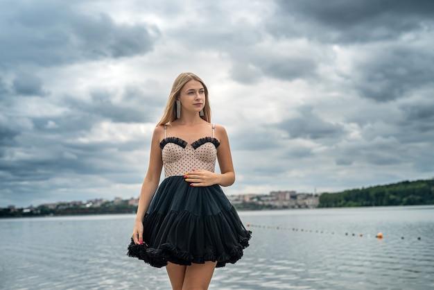 Beautiful woman in black fashion dress posing near lake, summer time