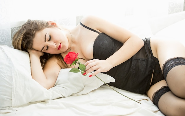 Beautiful woman in black lingerie lying in bed and holding red rose
