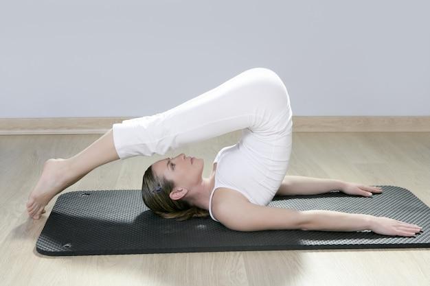 Beautiful woman in black mat yoga in gym