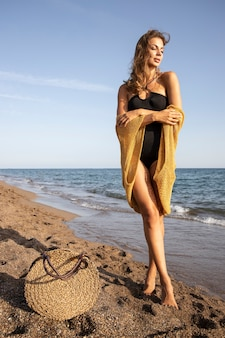 Beautiful woman in black swimsuit on the beach