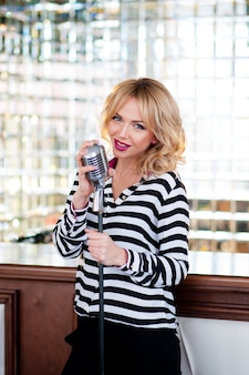 Beautiful woman, blonde, microphone. singing, beautiful smile