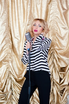Красивая женщина, блондинка, микрофон. пение, красивая улыбка