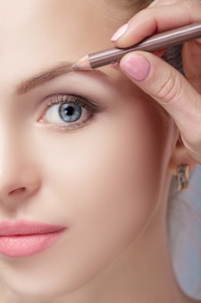 아름다운 여성 금발은 눈썹 화장을 위해 전문 연필을 사용합니다. 확대