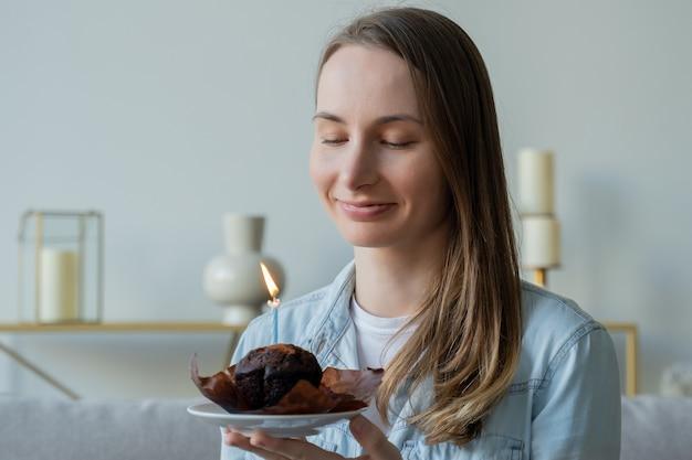 Красивая женщина, задувшая свечи на именинном торте Premium Фотографии