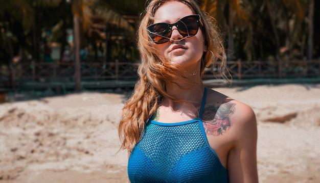 Beautiful woman in blue bikini on tropical beach. portrait of young woman at sea