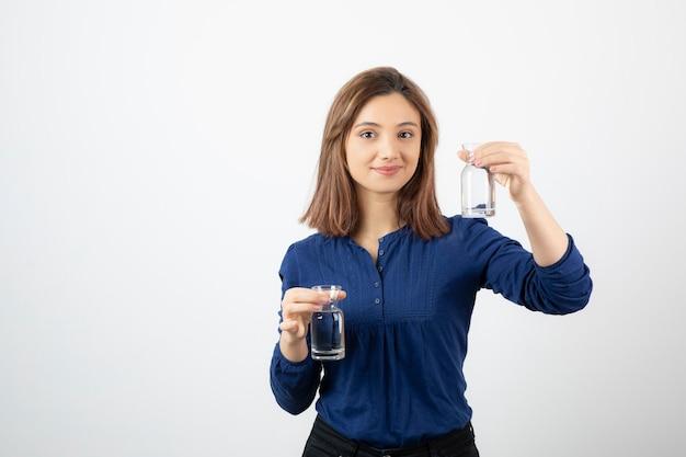 Bella donna in camicetta blu che tiene un bicchiere d'acqua su sfondo bianco.