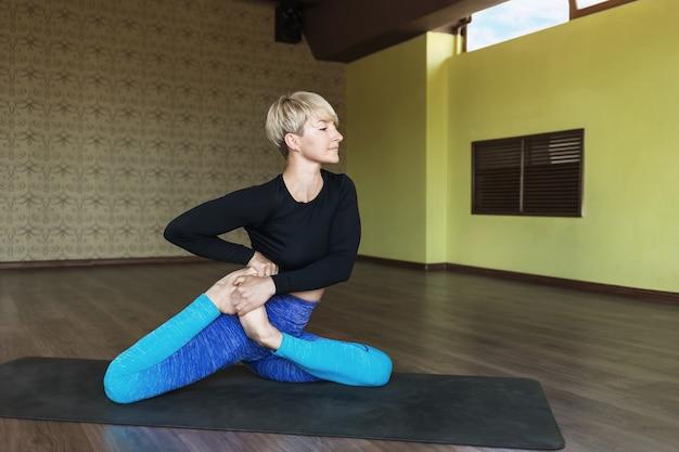 Beautiful woman in blue leggings and black rashguard practicing yoga