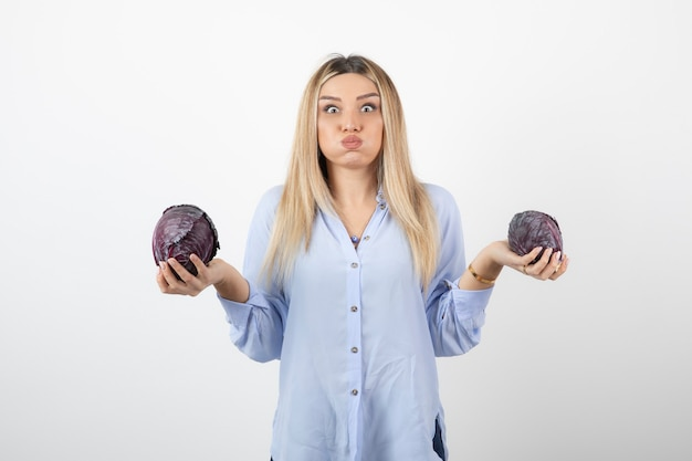 Beautiful woman in blue outfit holding purple cabbage over white wall.