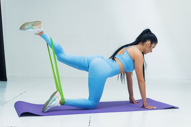 Beautiful woman in blue sportswear doing stretching exercises using fitness rubber bands in white