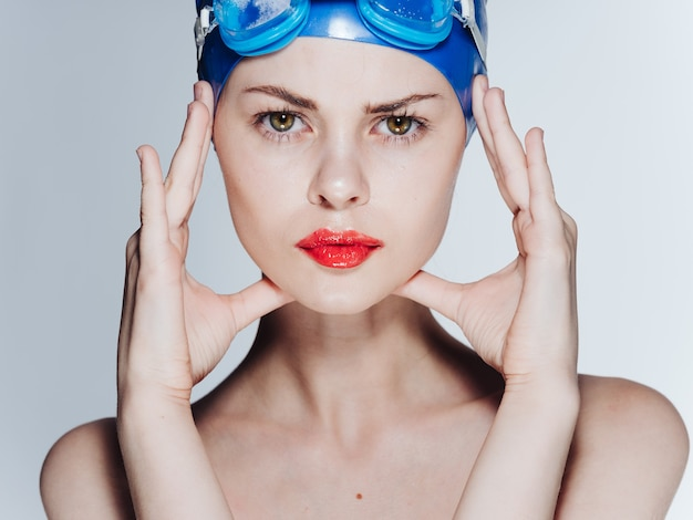 Beautiful woman in a blue swimming cap touches her face with her hands and glasses