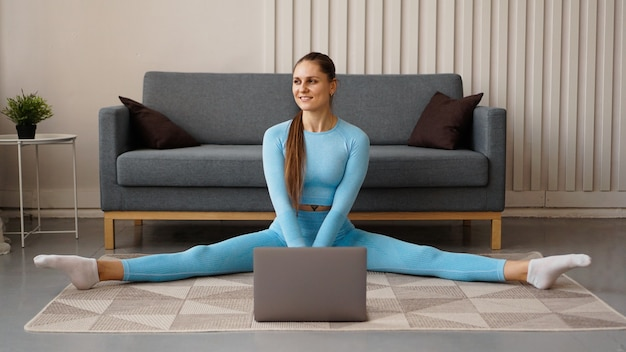 A beautiful woman in a blue tracksuit is stretching at home in front of a laptop. she sits in a transverse twine.