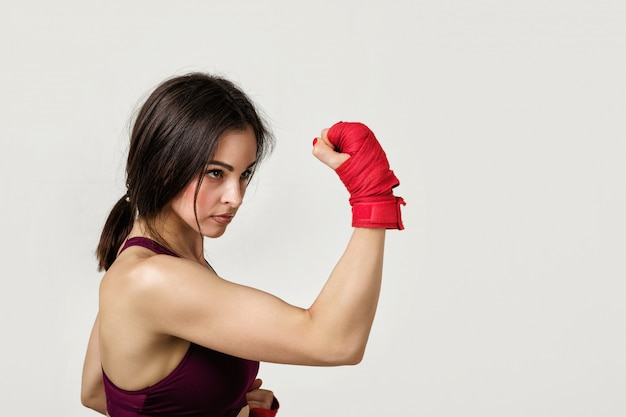 Beautiful woman boxer with red strap on wrist.