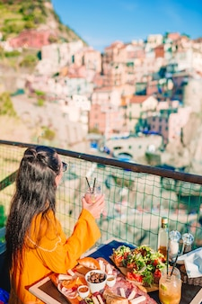 Beautiful woman on breakfast at outdoor cafe with amazing view in cinque terre