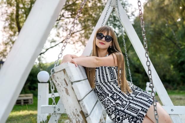 夏に白い木のブランコで呼吸する美しい女性