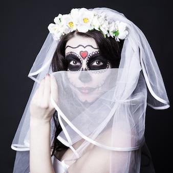 창조적 인 설탕 두개골 메이크업과 검은 배경 위에 신부 베일을 가진 아름 다운 여자 신부