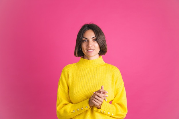 Beautiful woman in bright yellow sweater isolated on pink  look to front with confident smile