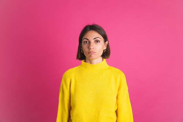 Beautiful woman in bright yellow sweater isolated on pink  look to front with unhappy sad disappointed face