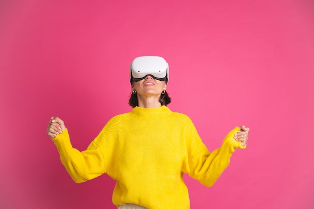 Beautiful woman in bright yellow sweater on pink  in virtual reality glasses happy excited overjoyed touch air