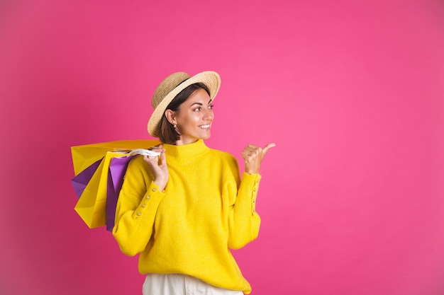 Beautiful woman in bright yellow sweater and straw hat on pink  hold shopping bags happy excited joyful point finger right space for text