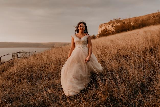 Красивая женщина брюнетка невеста в белом платье и костюме гуляет по высокой траве в поле летом