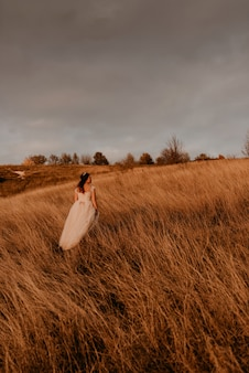 Beautiful woman brunette bride in white dress and suit are walking on tall grass in field in summer
