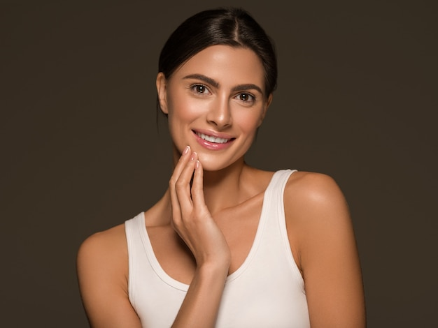 Beautiful woman brunette clean skin natural make up happy female teeth smile over black background