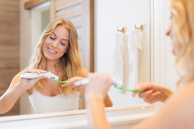 Beautiful woman brushing teeth in bathroom