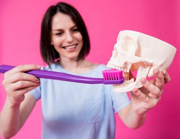 大きな歯ブラシを使用して人工頭蓋骨の歯を磨く美しい女性