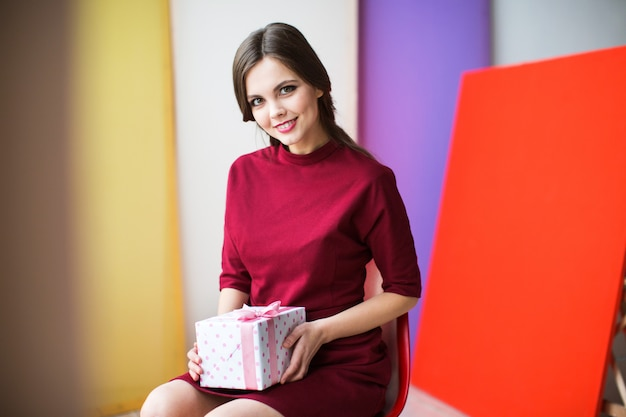 Beautiful woman in a burgundy dress holding a gift box.