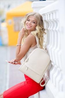 エレガントな赤いスカートと白いシャツの美しい女性のビジネス女性が電話でselfieを取る