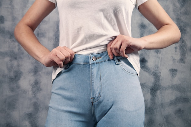 Beautiful woman buttons up blue jeans