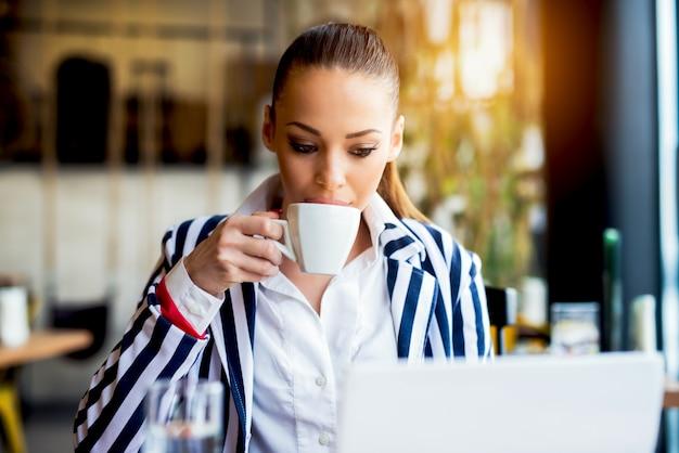 Beautiful woman at cafe bar drinking coffee.
