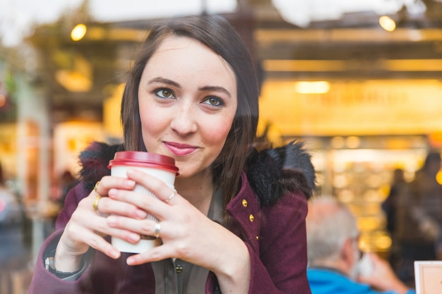 Beautiful woman in a cafe holding a cuf of tea