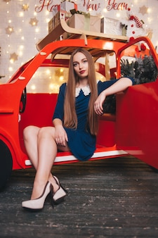 Beautiful woman in a car in the christmas interior.