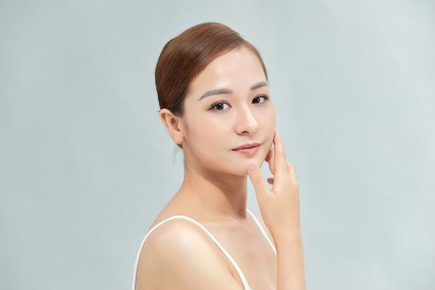 美しい女性が肌の顔をケアします