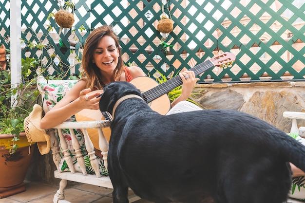 彼女の犬を愛dogし、屋外でギターを弾く美人。