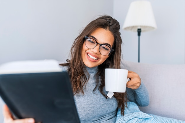 Beautiful woman in casual clothes and glasses is reading a book, holding a cup