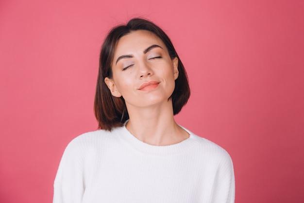 Bella donna in maglione bianco casual, sorriso carino isolato in piedi calmo viso chiuso gli occhi
