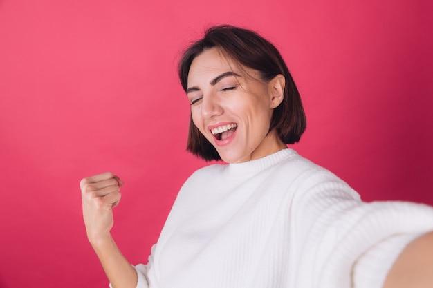 Bella donna in maglione bianco casual sulla parete rossa