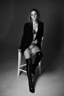 Beautiful woman of caucasian ethnicity posing sitting on a chair in a black jacket and lingerie