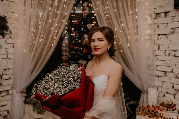 飾られたクリスマスツリーと花輪で新年とクリスマスを祝う美しい女性