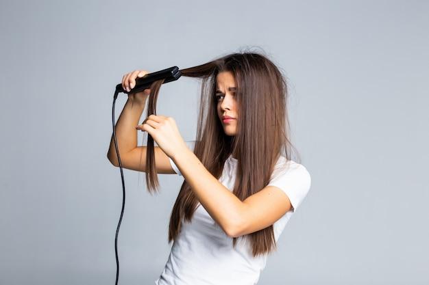 Raddrizzatore di capelli ceramico della bella donna isolato su bianco
