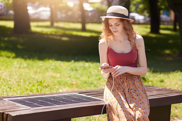 Beautiful woman charging her phone on free multipurpose solar panel, attractive female sitting on bench intown park. modern technology, free energy for everyone, solar panel, ecology concept.