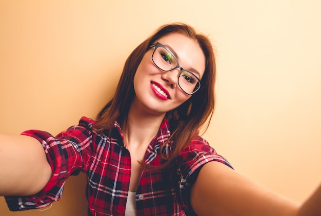 Beautiful woman in a checkered shirt makes emotional selfie. flash