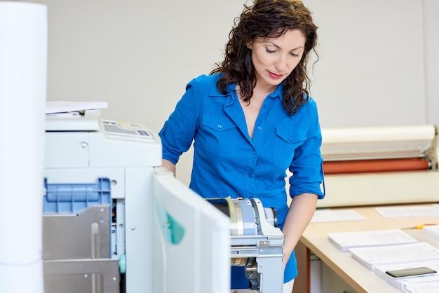 Beautiful woman checking printer mechanism
