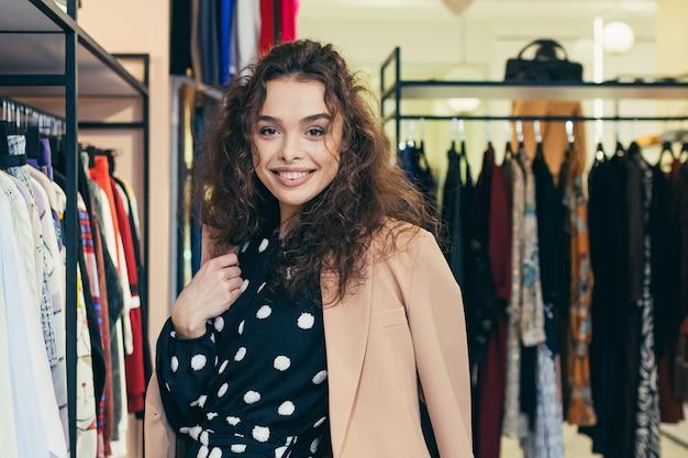 Красивая женщина выбирает одежду в магазине возле зеркала