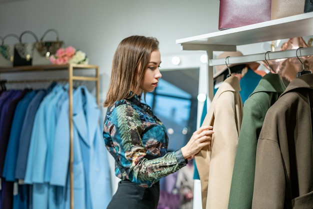 A beautiful woman chooses a coat in the store