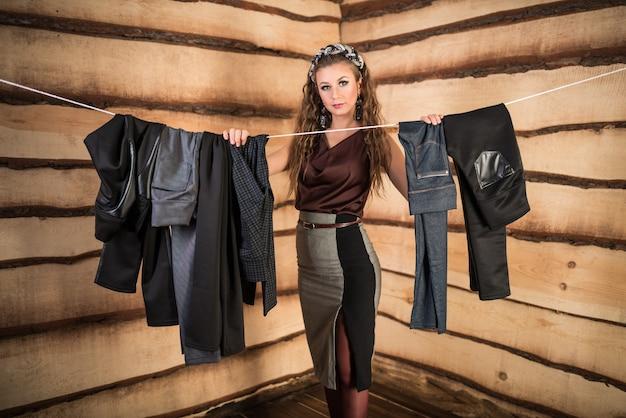 美しい女性は部屋のロープにぶら下がっている適切なズボンを選びます。ワードローブコレクションから希望のイベントのためのものを選ぶというコンセプト