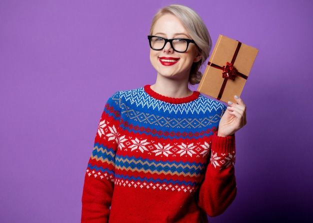Beautiful woman in christmas sweater and glasses holds gift box on purple background