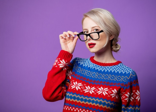 Beautiful woman in christmas sweater and glasses on purple background